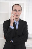 Business man at office holding finger up: idea or warning. Stock Photo