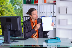 Business man in office pointing at clipboard with white page. Young business man in office pointing at clipboard with white page Royalty Free Stock Image
