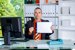 Business man in office pointing at clipboard with white page. Young business man in office pointing at clipboard with white page Royalty Free Stock Images