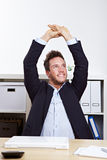 Business man in office stretching Stock Photography