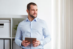 Business man in office with tablet Stock Images