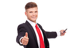 Business man okay with marker. Young business man presenting something in his back with a marker and showing thumbs up while smiling to the camera. isolated on stock image