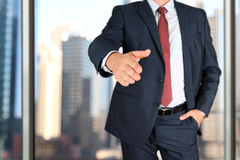 A business man with an open hand extended to handshake Stock Photo
