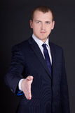 Business man with open hand ready to handshake over dark backgro Royalty Free Stock Photos