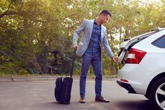 Business man opens car trunk stock photos