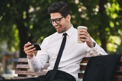 Business man outdoors in the park play games by phone drinking coffee. Image of handsome business man outdoors in the park play games by phone drinking coffee stock image