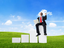Business Man Outdoors Sitting on a Bar Graph Celebrating.  Royalty Free Stock Photo