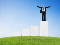 Business Man Outdoors Standing on a Bar Graph with Arms Raised.  Royalty Free Stock Photos