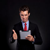 Business man with pad shows ok. Portrait of a young business man standing against a black background holding a tablet and showing the thumbs up sign while Royalty Free Stock Photos