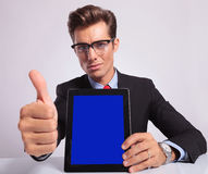 Business man pad thumb up. Young business man presenting his tablet and showing thumbs up sign at the desk while looking at the camera, on a gray background Stock Photo
