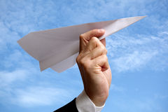 Business man with paper airplane against blue sky Royalty Free Stock Photos