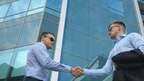 Business man passing a black briefcase to his partner. Colleagues shake hands outdoor in the city background. Two young. Businessmen meeting near office and stock video footage