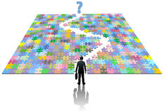 Business man path search puzzle solution. A business man searches a jigsaw puzzle to find a path to a solution Stock Image