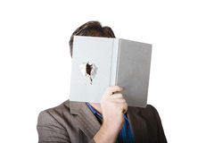 Business man peeking through spyhole in book Royalty Free Stock Images
