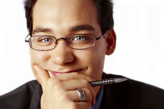 Business man with pen. And hand on chin, looking impish stock images