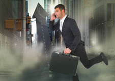 Business man on phone with briefcase running across arrow shaped road in street with flares Stock Images