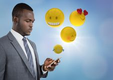 Business man on phone with emojis and flare against blue background Stock Image