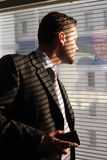 Business man with phone looking through window blinds Royalty Free Stock Photography