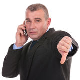 Business man on phone shows thumb down Royalty Free Stock Images