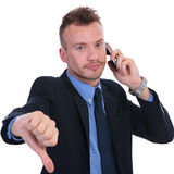 Business man on the phone shows thumb down Royalty Free Stock Image