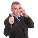 Business man on phone shows thumbs up Royalty Free Stock Image