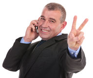 Business man on phone shows victory Stock Photography