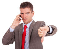 Business man on phone thumb down Royalty Free Stock Photo