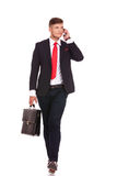Business man on phone walks Stock Photo