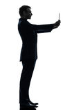 Business man  photographing digital tablet  silhouette Royalty Free Stock Photo