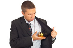 Business man with piggybank. Business man putting/ remove a gold piggy bank in/from interior of jacket isolated on white background stock photo