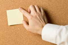 Business man pinning empty yellow sticky paper memo note on cork board. With copy space stock photos