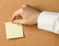 Business man pinning empty yellow sticky paper memo note on cork board. With copy space royalty free stock photography