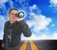 Business Man Planning for the Future. A business man is looking through binoculars. There are clouds behind him and a road. Can represent the future and planning Stock Photography