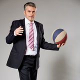 Business man playing with a basketball at the Stock Images