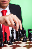 Business man playing chess black makes first move. Business man playing chess game selective focus black makes first move. on green background Royalty Free Stock Images