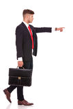 Business man point to side. Side view picture of a young business man holding a briefcase and pointing while walking forward, away from the camera. isolated on Stock Photos