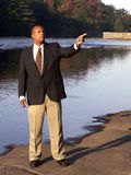 Business man pointing. Outside standing next to river shot in hard natural light Stock Images