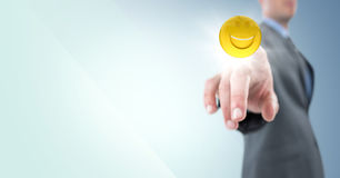 Business man pointing at emoji with flare against blue background Stock Photos