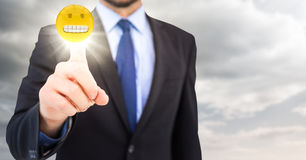 Business man pointing at emoji with flare in cloudy sky Royalty Free Stock Photography