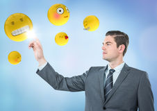 Business man pointing at emojis against blue background Stock Photography