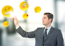Business man pointing at emojis against blurry grey office. Digital composite of Business man pointing at emojis against blurry grey office Royalty Free Stock Photography