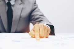 Business man pointing a finger at graph document royalty free stock photo
