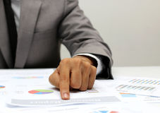 Business man pointing a finger at graph document stock photos