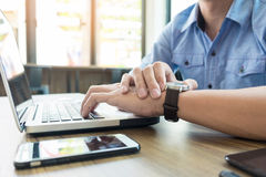 Business man pointing his watch with his finger at office Royalty Free Stock Photography