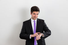 Business man is pointing at his watch and smiling Stock Photo