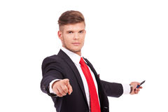 Business man pointing & presenting. Young business man pointing at the camera with a smile on his face while presenting something with a marker in his back stock photography