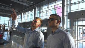 Business man pointing something to his colleague in sunglasses at timetable board screen. Two young businessmen looking. At flight schedule at airport. Checks stock video
