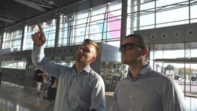 Business man pointing something to his colleague in sunglasses at timetable board screen. Two young businessmen looking. At flight schedule at airport. Checks stock video footage