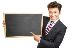 Business man pointing to empty chalkboard Royalty Free Stock Image