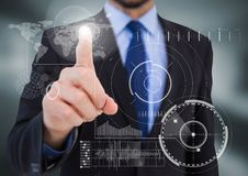 Business man pointing at white interface with flare in blurry grey room Stock Image